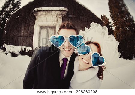 A Beautiful Bride In A White Fur Coat And A Groom In Cheerful Glasses In The Shape Of Heart In The S