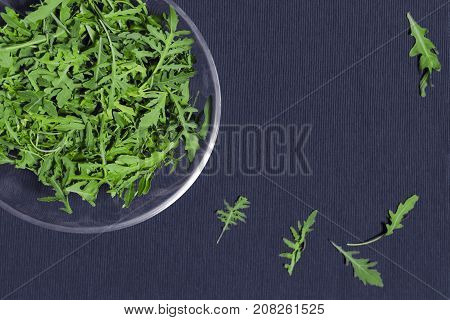 Green rucola salad in a dish on a blue napkin