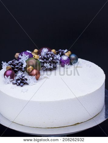 A cake for a Christmas holiday or a new year. A cake with chocolate cones and Christmas-tree toys is made of chocolate. Cake on snow background
