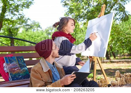 A guy with a beard in a red hat looks like a beautiful blonde girl paints a painter