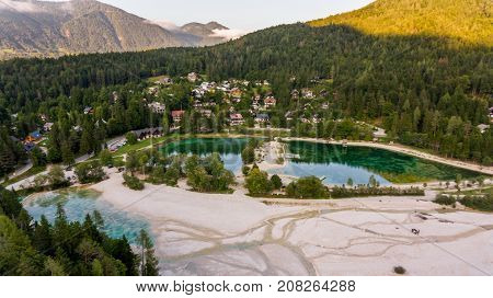 Aerial view of crystal clear lake surrounded with town. Jasna near Kranjska Gora, Slovenia.