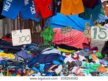 Dumaguete Philippines - 9 September 2017: Cheap clothes on rustic street market. Streetwear for sale. Price drop down for clothes. Tshirt and short pile on market's table. Second hand clothes store