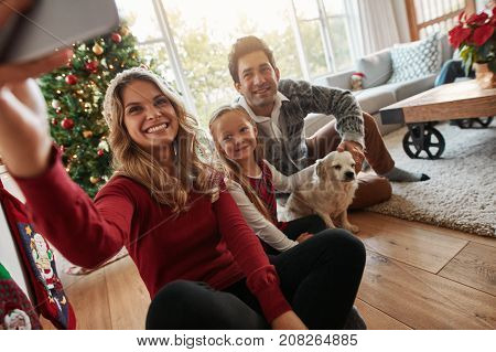 Young happy family of three taking a photo of themselves in living room on Christmas eve. Caucasian family with dog sitting by christmas tree at home taking selfie with mobile phone.