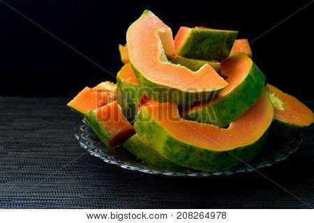 Papaya cut on black background. Cut papaya on plate served for vegetarian breakfast. Healthy and sweet tropical fruit. Exotic fruit with juicy orange flesh and green skin. Fresh papaya for food banner