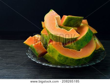 Papaya cut on black background. Cut papaya on plate served for vegetarian breakfast. Healthy and sweet tropical fruit. Exotic fruit with juicy orange flesh and green skin. Ripe raw papaya for snack