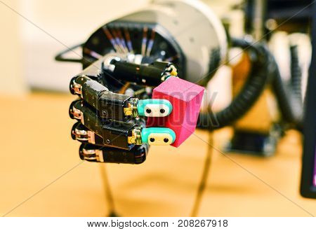 Robot Hand Holding a Red Cube in Research Laboratory. Machine Learning Concept. Authentic Shot.