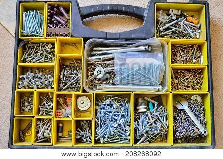 A box with variety of nails screws nuts bolts and washers.