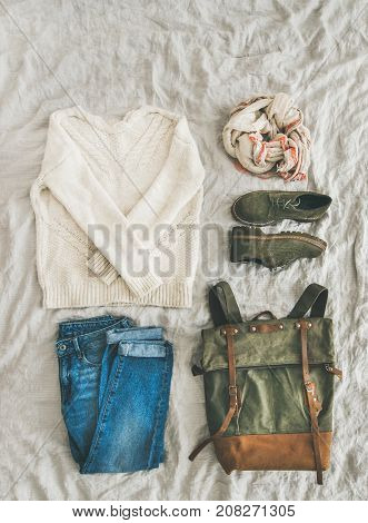 Flat-lay of Fall lady' s clothes outfit. Ecru colored knitted woolen sweater, linen scarf, denim jeans, haki suede boots, backpack over grey linen bed blanket, top view, copy space. Trendy Autumn look