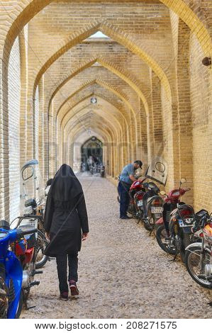Fars Province Shiraz Iran - 19 april 2017: Arched corridor in back street of Vakil Bazaar muslim woman wearing black chador goes into the distance.
