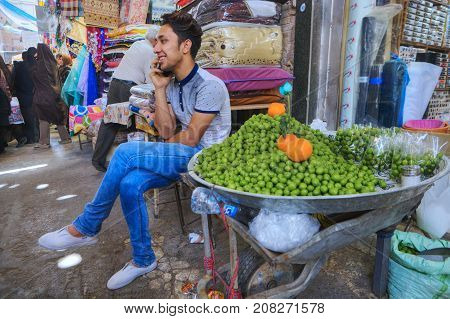 Fars Province Shiraz Iran - 19 april 2017: A young trader of sour green plums talks on the phone in anticipation of buyers.