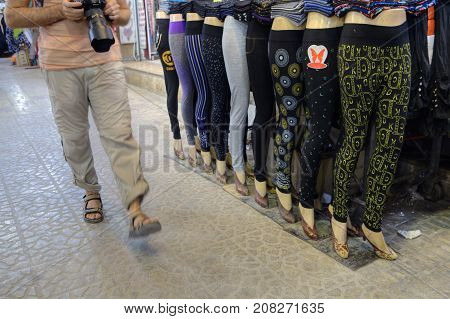 Fars Province Shiraz Iran - 19 april 2017: A tourist walks past a number of walking mannequins dressed in women's leggings a corridor inside the Vakil bazaar.