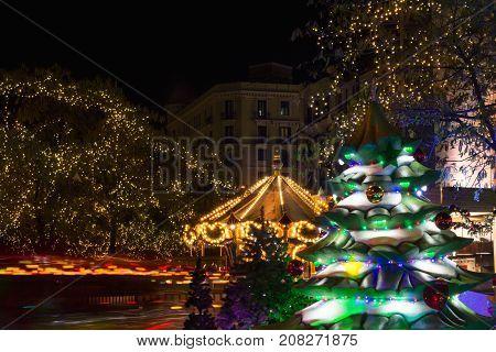 Night image of christmas carousel lights and Christmas tree