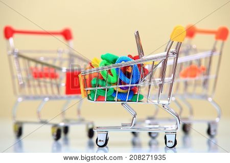 Sales background. Colorful elastic hair bands in small shopping trolley closeup.