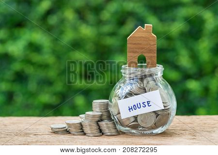 glass jar bottle labeled as house with full of coins and miniature wooden house on top and stack of coins as home property or mortgage investment concept.