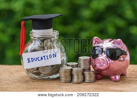 glass jar with full of coins and graduates hat label with Piggybank and stack of coins as Education education or savings concept.