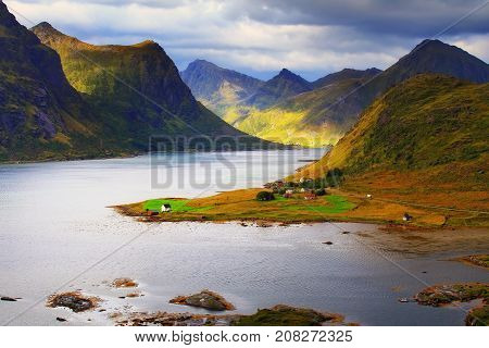 Sunny Lofoten day. Beautiful fjord in autumn day. Colorful rocks and blue water of Norway.
