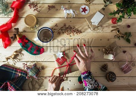 Woman Decorating A Christmas Present, Surrounded By Festive Decorative Items, On Rustic Wood Table