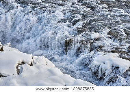 Rough river with snow rocky shore in Iceland. Water falls from the cascade. Horizontal.
