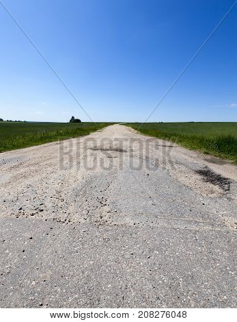 The place of connection of an asphalted and not asphalt road in an agricultural field with cereals. landscape in summer with blue sky