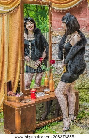 Woman in retro style looks in the mirror outdoors