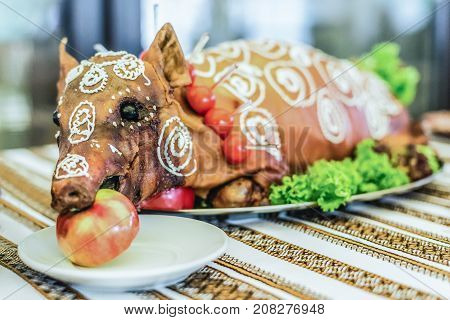 Cooked suckling pig with an apple in his mouth on a white plate on banquet table close up