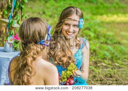 Two sisters twins in the garden with flowers and fruits. Beautiful, happy, smiling sisters twins outdoor