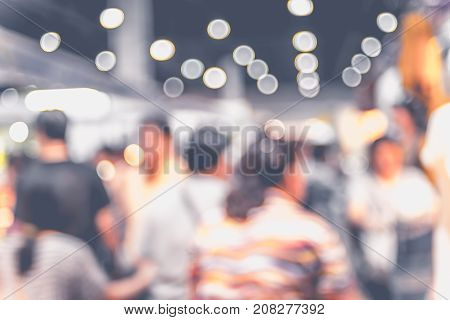 Blurred background: crowd of people in expo fair with bokeh light Vintage filter.
