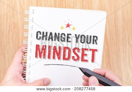 Change your mindset word on white ring binder notebook with hand holding pencil on wood tableBusiness concept