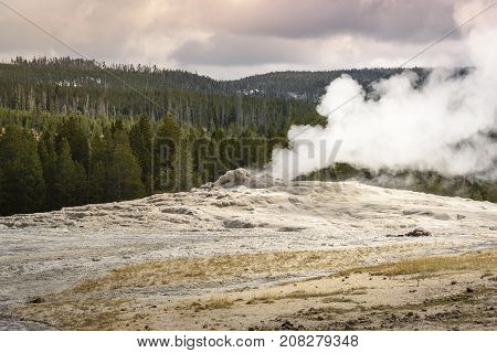 Old faithful eruption seen from the Upper Geyser Basin at Yellowstone National Park