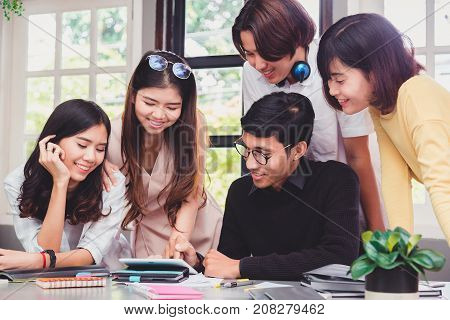 Group of five young euphoric students watching exam results in a laptop in a table of an university campus bar.