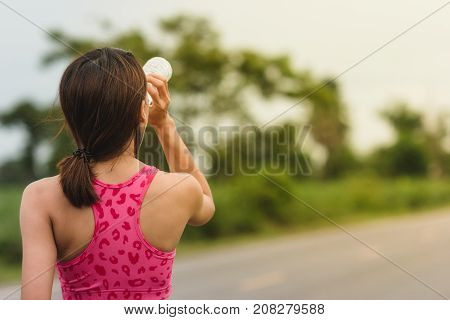 Women are drinking water from bottles to quench thirst from exercise.Girl quenches thirst after fitness outdoorsHealthy lifestyle.