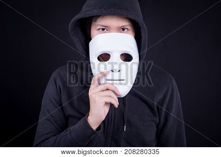 Mystery man holding white mask for hide his face. Anonymous social masking or halloween concept.