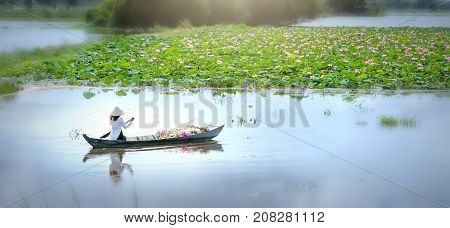 Long An, Vietnam - September 24th, 2017: Farmers carrying lilies boating through rural marshland in early morning brought agricultural trade market in the Mekong Delta, Long An, Vietnam