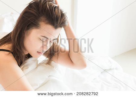 Closeup woman waking up with sore head on bed health care and medical concept selective focus