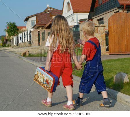 Two Children Walking On The Street