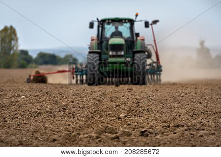 Close-up of crop with Tractor ploughing field in the background. Farmer with tractor seeding.