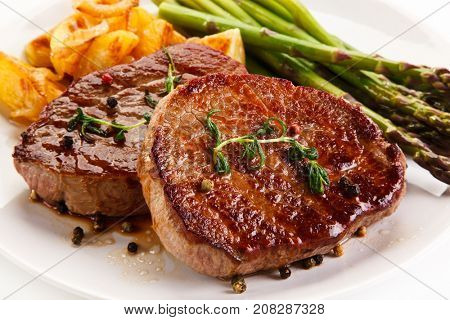 Grilled beef steaks,chips and asparagus on white background