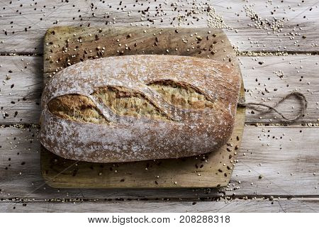 high-angle shot of a loaf of spelt bread on a chopping board, placed on a white rustic wooden table