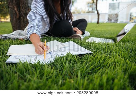 Cropped photo of student girl in casual wear, keeping records in paper notebook while studying online with laptop, sitting on grass, outdoor