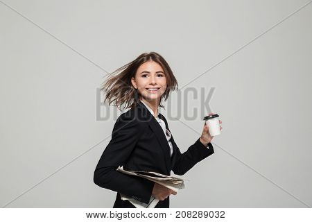 Portrait of a young attractive businesswoman in suit holding take away coffee cup and a newspaper while running and looking at camera isolated over white background