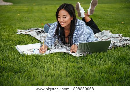 Beautiful asian female student, taking notes, lying on checkered plaid in park