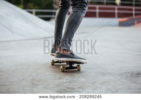 Cropped image of an african male teenager riding on skateboard at a skate park