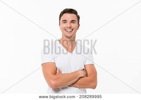 Close up portrait of a joyful young man in a white t-shirt standing with arms folded and looking at camera isolated over white background