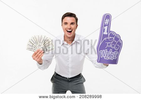 Portrait of an excited amused man in white shirt holding bunch of money banknotes and wearing foam finger isolated over white background