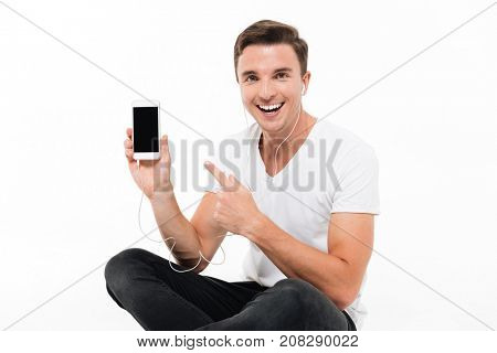 Portrait of a happy excited man in earphones pointing finger at blank screen mobile phone while sitting and looking at camera isolated over white background