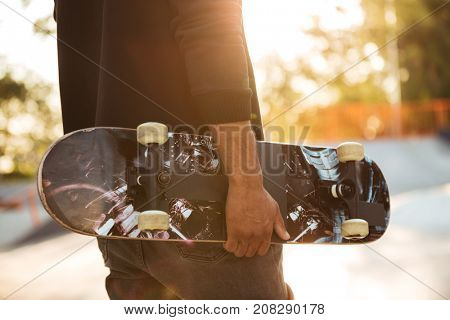 Close up of an african man skateboarder standing with a skateboard at sunset city park