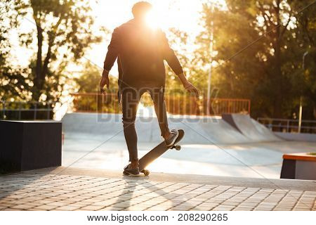African skateboarder skating on a concrete skateboarding ramp at the skate park