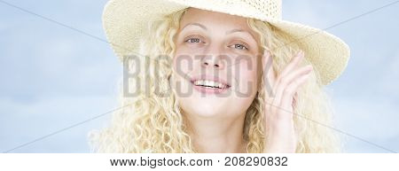 Blonde curly girl with summer hat