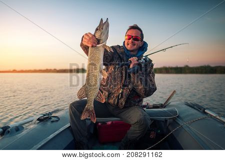 Happy amateur angler holds Pike fish sitting in the boat on the lake during sunrise