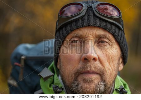Portrait of mature backpacker in an autumn forest